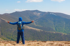 Mountaineer reaches the top of a mountain in sunny Stock Images
