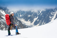 Mountaineer reaches the top of a snowy mountain. In a sunny day royalty free stock photos