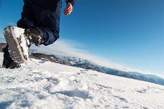 Mountaineer reaches the top of a snowy mountain. Stock Image