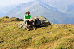 Mountaineer resting on rock in front of mountain panorama in Hohe Tauern Alps Stock Photos