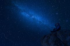 Mountaineer look at night sky with stars. Mountaineer on rock enjoying look at night sky with stars and milky way, hiking lifestyle, mans on top stock image