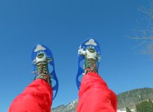 Mountaineer's legs with snowshoes for excursions in the mountain Royalty Free Stock Images