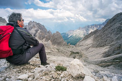 Mountaineer sitting on the rock admiring the mountain panorama Stock Image