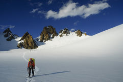 Mountaineer on a snow-covered glacier in the eveni Stock Photos