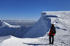 Mountaineer on snowy summit. Rear view of female mountaineer on snowy summit of Helvellyn mountains in Winter, Lake District National Park, Cumbria, England Stock Photography