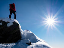 Mountaineer standing at the top of the mountain. Stock Photos