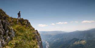 Mountaineer stands on the edge of world Royalty Free Stock Photos