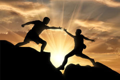 Mountaineer takes a helping hand to his partner. Help concept Royalty Free Stock Image