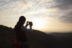 Mountaineer taking a photo of a sunset. In Huesca, Spain Stock Photos