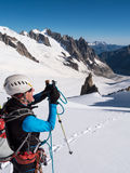 Mountaineer taking picture with a camera in the mountains. Royalty Free Stock Photo