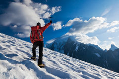 Mountaineer top mountain. A male mountaineer walking uphill on a glacier. Mont Blanc, France royalty free stock image