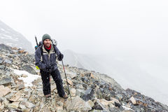 Mountaineer tourist walking mountain trail storm snowing weather. Mountaineer guy tourist walking hiking ascending mountain trail path snowing storm weather Royalty Free Stock Photos