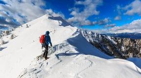 Mountaineer walking on the snowy slope. Of the Dovska Baba mountain in Karavanke range, Slovenia Royalty Free Stock Image