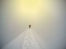 Mountaineer walking up along a snowy ridge on Mont Blanc Stock Photos