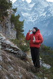 Mountaineer at winter snowy peaks background resting and drinking from vacuum flask metal cup stock image