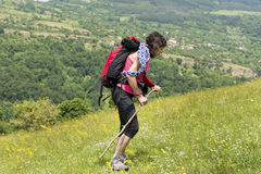 Mountaineer woman with backpack on a meadow with flowers Royalty Free Stock Photos