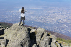 Mountaineer woman on top of a mountain looking the city view. Mountaineer woman on top of a mountain looking the city of ,Bulgaria Royalty Free Stock Photography