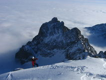 Mountaineering. A mountaineer ascending snow slope. Mountain rising from clouds in background Stock Photo