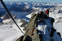 Mountaineering. Winter climbing in the Alps. Climber with rope on a ridge Stock Image