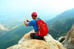 A mountaineering enthusiast takes a cell phone photo at the cliff edge of Songshan`s Shaolin mountain peak. Mountaineering enthusiasts, China`s , Shaolin hill Royalty Free Stock Photo