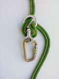 Mountaineering equipment used in belay abseil or rappel. Figure of eight friction device rigged through green rope Royalty Free Stock Photography