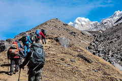 Mountaineering Expedition moving toward high Altitude Mountain. Members of Mountaineering Expedition moving up on yellow steep Slope towards high Altitude stock photos