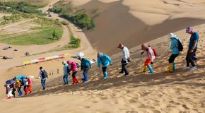 Mountaineering team goes down the sand dune, srgb image