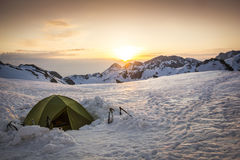 Mountaineering tent in the snow. Mountaineering tent in the winter landscape surrounded by the mountain peaks at the sunset stock images