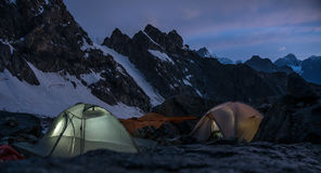 Mountaineers camps in very high craggy mountains beside glacier. Stock Image