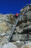 Mountaineers climbing down a steep ladder royalty free stock photography