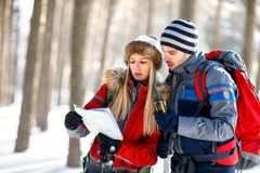 Mountaineers couple looking for path on map. In wood on winter Royalty Free Stock Photos