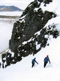 Mountaineers descending. Two mountaineers descending a snow filled gully Stock Image