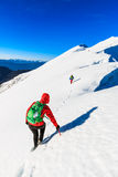 Mountaineers walking on the mountain ridge. Mountaineers walking on the snow covered Kosuta ridge in Karavanke range, Slovenia Royalty Free Stock Photography