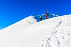 Mountaineers walking on the mountain ridge. Mountaineers walking on the snow covered Kosuta ridge in Karavanke range, Slovenia Royalty Free Stock Image
