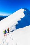 Mountaineers walking on the mountain ridge. Mountaineers walking on the snow covered Kosuta ridge in Karavanke range, Slovenia Stock Photography