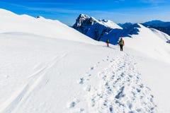 Mountaineers walking on the mountain ridge. Mountaineers walking on the snow covered Kosuta ridge in Karavanke range, Slovenia Royalty Free Stock Images