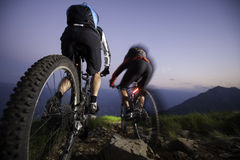 Mountaingike downhill by night - blurred motion. Two person by bike nightrace Stock Images