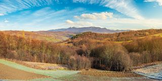 Mountainous countryside in late autumn. Panorama of mountainous countryside in late autumn. almost leafless forest on hill. gorgeous cloudscape above the ridge stock image