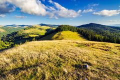 Mountainous early autumn landscape in evening. Light. beautiful view from the grassy meadow on hill. location Romania, Apuseni Natural Park royalty free stock photos