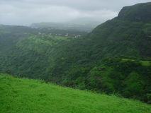 Mountainous green landscape. Scenic view of lush green forest on mountainous landscape with rainclouds Stock Photography