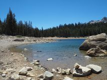 Mountainous Lake Scene in Mammoth. A lake in Mammoth, California surrounded by pine trees and snow-capped mountains on a sunny day stock photography