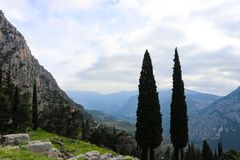 Mountainous landscape in Greece with cyprus trees in the foreground seen from Delphi ruins high in mountians. A Mountainous landscape in Greece with cyprus trees Stock Photography