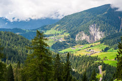 Mountainous landscape. Scenic view of a forested mountainous landscape with green fields of a valley in the background Royalty Free Stock Photo
