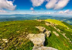 Mountainous landscape in summer. Lovely scenery with rocky formation on the grassy hill under the blue sky with some clouds royalty free stock image