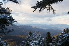 Mountainous landscape during winter, with clouds and sun rays, through a frame of snowy fir trees. Mountainous landscape in Greece during winter season, with stock image