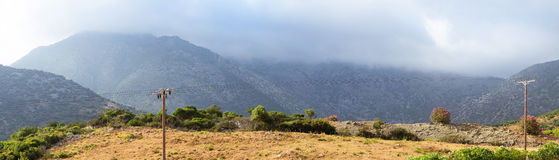 Mountainous nature Bali, Crete. Mountainous nature of resort village Bali on island Crete in Greece. Low dark clouds hide tops of mountains, morning cool and fog Royalty Free Stock Photo