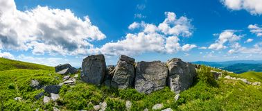 Mountainous panorama with boulders on hillside. Beautiful summer landscape in fine weather under the lovely cloudscape Royalty Free Stock Photos
