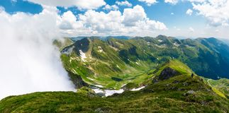 Mountainous panorama with rising clouds. Beautiful landscape with some snow on grassy hillsides. popular destination for hiking in Fagaras mountains of Romania Stock Image