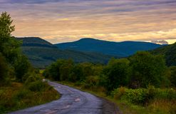 Mountainous road on cloudy sunrise. Lovely landscape in early autumn Stock Photos