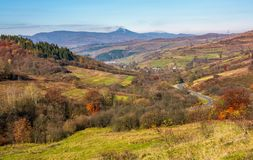 Mountainous rural area in late autumn. Trees with reddish foliage on green grassy hills. mountain ridge with high peak in the distance Royalty Free Stock Photos